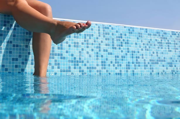 The feet of a young woman splashing in the pool